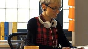 Θηλυκός γραφικός σχεδιαστής που εργάζεται στον υπολογιστή ενώ έχοντας το μαύρο καφέ απόθεμα βίντεο