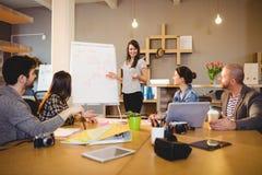 Θηλυκός γραφικός σχεδιαστής που διοργανώνει τη συζήτηση με τους συναδέλφους στοκ φωτογραφίες