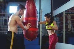 Θηλυκός εγκιβωτισμός άσκησης μπόξερ με punching την τσάντα Στοκ εικόνες με δικαίωμα ελεύθερης χρήσης