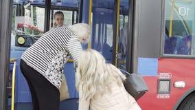 Θηλυκός επιβάτης που βοηθά την ανώτερη γυναίκα για να επιβιβαστεί στο λεωφορείο φιλμ μικρού μήκους