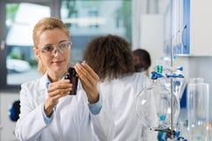 Θηλυκός επιστημονικός ερευνητής στο εργαστήριο που κάνει την έρευνα, γυναίκα που λειτουργεί με τις χημικές ουσίες πέρα από την ομ Στοκ φωτογραφία με δικαίωμα ελεύθερης χρήσης
