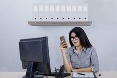 Θηλυκός επιχειρηματίας που εξετάζει το κινητό τηλέφωνο Στοκ Εικόνες