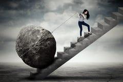 Θηλυκός επιχειρηματίας που φέρνει τη μεγάλη πέτρα στο σκαλοπάτι Στοκ Φωτογραφία