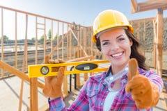 Θηλυκός εργάτης οικοδομών με τους αντίχειρες επάνω στη φθορά επιπέδων εκμετάλλευσης Στοκ φωτογραφία με δικαίωμα ελεύθερης χρήσης