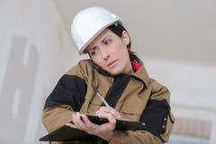 Θηλυκός εργάτης οικοδομών που μιλά στο τηλέφωνο γράφοντας τις σημειώσεις Στοκ Εικόνες