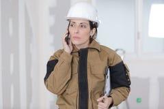 Θηλυκός εργάτης οικοδομών που μιλά στο τηλέφωνο στο εργοτάξιο Στοκ φωτογραφίες με δικαίωμα ελεύθερης χρήσης