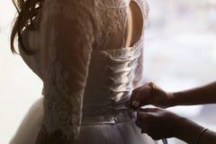 Θηλυκός δεσμός βοήθειας χεριών στο πίσω μέρος του φορέματος Στοκ φωτογραφία με δικαίωμα ελεύθερης χρήσης