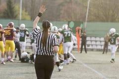Θηλυκός διαιτητής αμερικανικού ποδοσφαίρου που δίνει τα σήματα και το θολωμένο παιχνίδι Στοκ Εικόνες