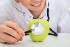 Θηλυκός διαιτολόγος που εξετάζει το πράσινο μήλο Στοκ Εικόνα