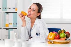 Θηλυκός διατροφολόγος που τρώει μια πορτοκαλιά φέτα στο γραφείο της Στοκ εικόνες με δικαίωμα ελεύθερης χρήσης