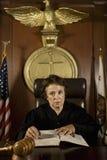 Θηλυκός δικαστής που αναφέρεται στο βιβλίο νόμου Στοκ εικόνες με δικαίωμα ελεύθερης χρήσης