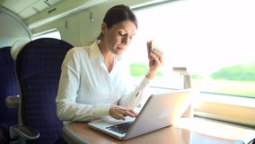 Θηλυκός κάτοχος διαρκούς εισιτήριου στο τραίνο που χρησιμοποιεί το lap-top ταυτόχρονα τρώγοντας το σάντουιτς φιλμ μικρού μήκους