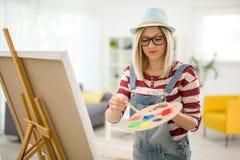 Θηλυκός καλλιτέχνης που αναμιγνύει τα χρώματα σε μια παλέτα Στοκ φωτογραφία με δικαίωμα ελεύθερης χρήσης