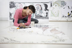 Θηλυκός καλλιτέχνης που επισύρει την προσοχή σε μεγάλο χαρτί Στοκ εικόνες με δικαίωμα ελεύθερης χρήσης