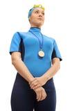 Θηλυκός κολυμβητής με το χρυσό μετάλλιο που ακούει το εθνικό ύμνο Στοκ Εικόνα