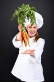 Θηλυκός μάγειρας άσπρο σε ομοιόμορφο με τη δέσμη των καρότων Στοκ Εικόνες