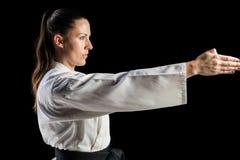 Θηλυκός μαχητής που εκτελεί karate τη θέση Στοκ Εικόνες