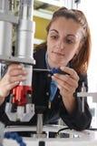 Θηλυκός μηχανικός μαθητευόμενων που εργάζεται στη μηχανή στο εργοστάσιο Στοκ φωτογραφίες με δικαίωμα ελεύθερης χρήσης