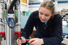 Θηλυκός μηχανικός μαθητευόμενων που εργάζεται στη μηχανή στο εργοστάσιο Στοκ Φωτογραφία