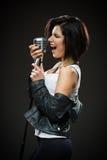 Θηλυκός μουσικός βράχου που κρατά το Mike Στοκ Φωτογραφίες