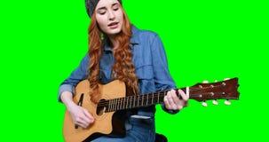 Θηλυκός μουσικός που τραγουδά παίζοντας την κιθάρα απόθεμα βίντεο