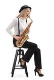 Θηλυκός μουσικός τζαζ που κάθεται σε μια καρέκλα που παίζει ένα saxophone Στοκ εικόνα με δικαίωμα ελεύθερης χρήσης