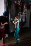 Θηλυκός μπόξερ στα εγκιβωτίζοντας γάντια που εκπαιδεύει με τον εκπαιδευτή και το boxi της Στοκ Εικόνες