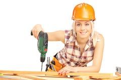 Θηλυκός ξυλουργός με το κράνος στην εργασία που χρησιμοποιεί τη μηχανή διατρήσεων χεριών Στοκ φωτογραφίες με δικαίωμα ελεύθερης χρήσης