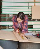 Θηλυκός ξυλουργός που μετρά το ξύλο με την κλίμακα Στοκ Εικόνα