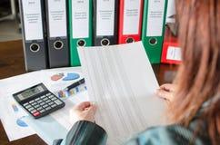 Θηλυκός λογιστής που ελέγχει τα οικονομικά έγγραφα Στοκ φωτογραφία με δικαίωμα ελεύθερης χρήσης