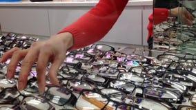 Θηλυκός οπτικός που παίρνει τα γυαλιά στον πελάτη απόθεμα βίντεο