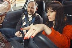Θηλυκός οδηγός στο πορτοκαλί πουλόβερ με το αρσενικό στο κάθισμα επιβατών ` s Στοκ φωτογραφία με δικαίωμα ελεύθερης χρήσης