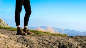 Θηλυκός οδοιπόρος πάνω από το βουνό που φορά τις μπότες πεζοπορίας στοκ φωτογραφία