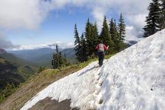 Θηλυκός οδοιπόρος που διασχίζει το χιόνι στην κορυφή βουνών Στοκ εικόνα με δικαίωμα ελεύθερης χρήσης