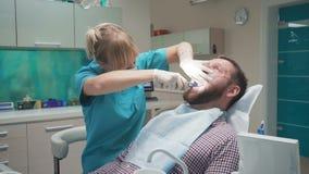 Θηλυκός οδοντίατρος που εξάγει το υπομονετικό δόντι ` s steadicam απόθεμα βίντεο