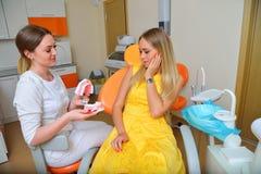 Θηλυκός οδοντίατρος που εξηγεί πώς να φροντίσει δόντια Στοκ Φωτογραφία