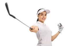 Θηλυκός παίκτης γκολφ που δείχνει ένα γκολφ κλαμπ και που κρατά μια σφαίρα Στοκ Φωτογραφία