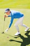 Θηλυκός παίκτης γκολφ που παίρνει τη σφαίρα γκολφ Στοκ Εικόνα