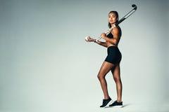 Θηλυκός παίκτης χόκεϋ πέρα από το γκρίζο υπόβαθρο Στοκ Εικόνες