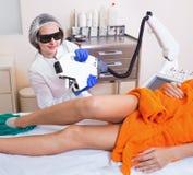 Θηλυκός πελάτης που κάνει την αφαίρεση τρίχας λέιζερ από τα πόδια Στοκ Εικόνες