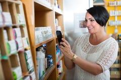 Θηλυκός πελάτης που κρατά το κινητό τηλέφωνο στο φαρμακείο στοκ εικόνα