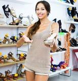 Θηλυκός πελάτης που παρουσιάζει επιθυμητό παπούτσι στη μπουτίκ Στοκ εικόνα με δικαίωμα ελεύθερης χρήσης