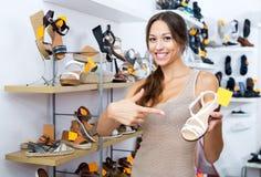 Θηλυκός πελάτης που παρουσιάζει επιθυμητό παπούτσι στη μπουτίκ Στοκ φωτογραφία με δικαίωμα ελεύθερης χρήσης
