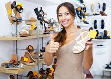 Θηλυκός πελάτης που παρουσιάζει επιθυμητό παπούτσι στη μπουτίκ Στοκ εικόνες με δικαίωμα ελεύθερης χρήσης