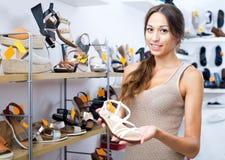 Θηλυκός πελάτης που παρουσιάζει επιθυμητό παπούτσι στη μπουτίκ Στοκ Φωτογραφίες