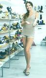 Θηλυκός πελάτης που παρουσιάζει επιθυμητό παπούτσι στη μπουτίκ Στοκ Εικόνες