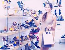 Θηλυκός πελάτης που παρουσιάζει επιθυμητό παπούτσι στη μπουτίκ Στοκ Εικόνα
