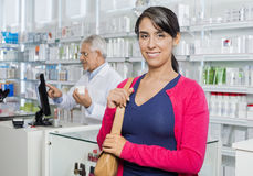 Θηλυκός πελάτης που χαμογελά ενώ φαρμακοποιός που εργάζεται στο φαρμακείο στοκ φωτογραφία με δικαίωμα ελεύθερης χρήσης