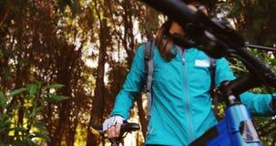 Θηλυκός ποδηλάτης βουνών που περπατά με το ποδήλατο φιλμ μικρού μήκους