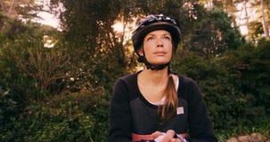 Θηλυκός ποδηλάτης βουνών που στέκεται με το ποδήλατο που ανατρέχει απόθεμα βίντεο